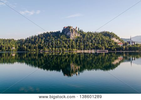 BLED SLOVENIA - 28TH MAY 2016: A view towards Bled Castle in Slovenia in the morning. Reflections can be seen in the water.