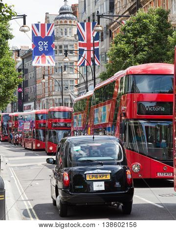 LONDON UK - 28TH JUNE 2016: A view along Oxford Street in London during the day. Large amounts of buses a black London taxi and union jack flags can be seen.