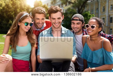 Friendly air. Happy and delighted group of young people using laptop and watching videos while being in the park