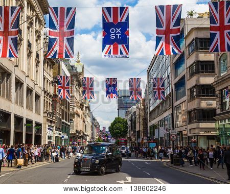 LONDON UK - 28TH JUNE 2016: A view along Oxford Street in London during the day. A black London taxi union jack flags and lots of people can be seen.