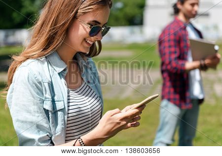 Phone usage. Cheerful and positive young woman using smart phone and young man standing in a background