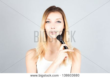 Blonde woman holding professional brush for blush. Make up artist.