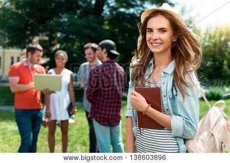 My usual day. Smiling and delighted young woman standing and holding copybook and looking at a camera with her friends communicating and using laptop in a background