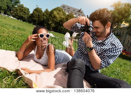 My photographer. Happy and confident young woman lying on the grass and smiling while cheerful young man making photos using camera