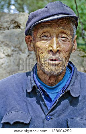 GUEILLIN CHINA - SEP 12: very old farmer in traditional blue working class uniform on Sep 12 2011 in Gueillin China. Farmer earn less than 30 percent than people with office jobs.