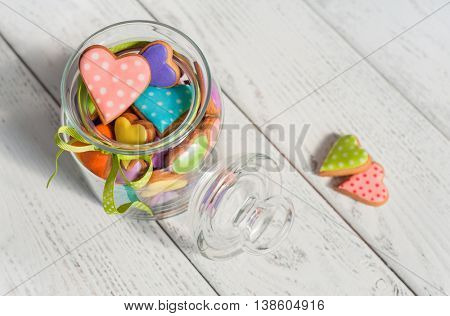 Colorful cookies in the shape of heart on wooden table.