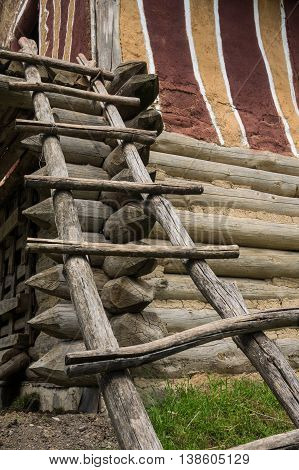 Wooden ladder leaning to the house. Renovated house of Trypillian culture.