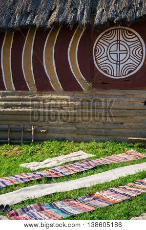 Long homespun mats striped multicolored spread out on the grass near the house. Renovated house of Trypillian culture.