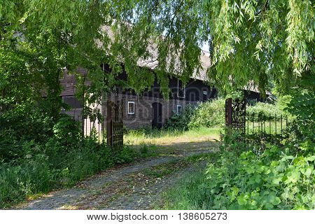 Old farm thatch black wood entrance fence trees