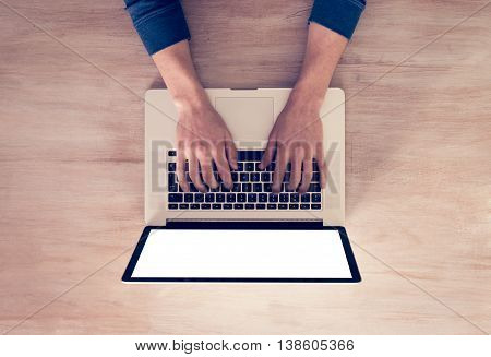 Man's hands using laptop with blank screen on desk in home interior. - Top View