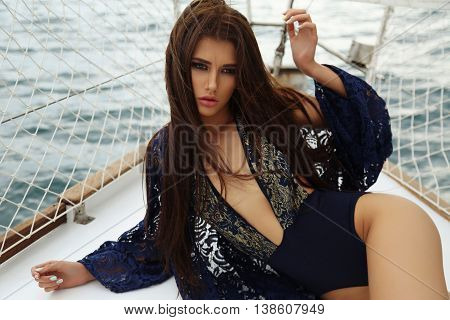 Sexy Woman With Dark Hair In Elegant Swimsuit Posing On Yacht