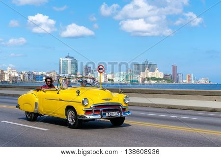 HAVANA,CUBA - JULY 14,2016 :  Old convertible car on the Havana malecon avenue with a view of the sea and the city skyline