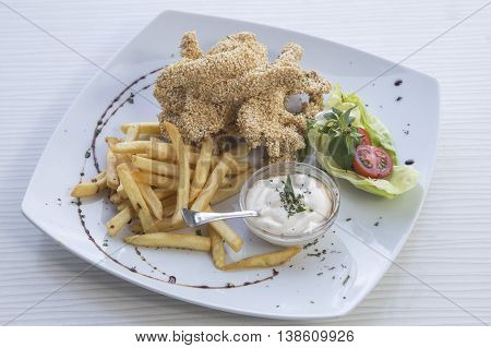 Fried chicken nuggets with sesame and french fries