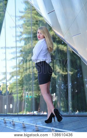 portrait of beautiful blond business woman standing in front of office building in the city