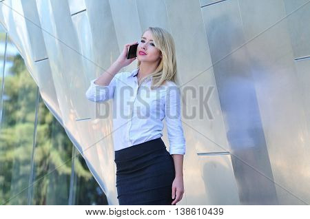 Professional corporate woman in business attire talking on mobile phone in the city