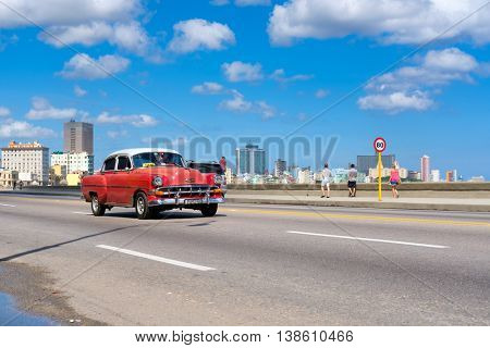 HAVANA,CUBA - JULY 14,2016 :  Classic car on the Havana malecon avenue with a view of the city skyline