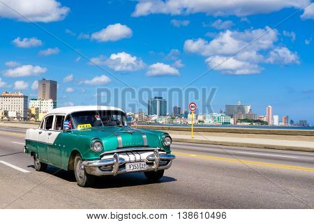 HAVANA,CUBA - JULY 14,2016 :  Classic car on the Havana malecon avenue with a view of the sea and the city skyline