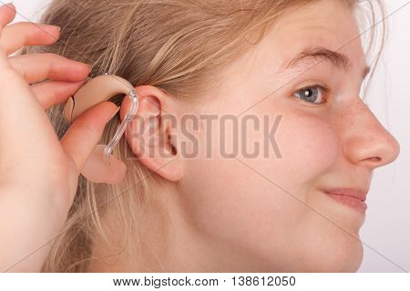 Portrait of a young woman trying to insert a hearing aid into ear