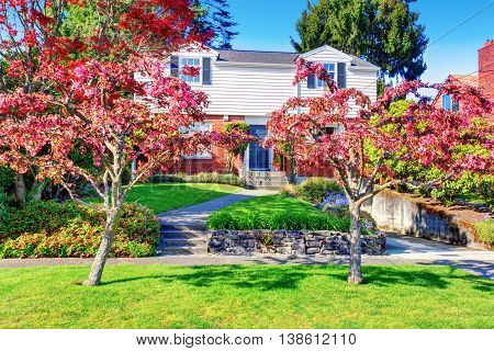 Beautiful Curb Appeal Of Brick House With Well Kept Lawn And Red Trees In The Front Garden.