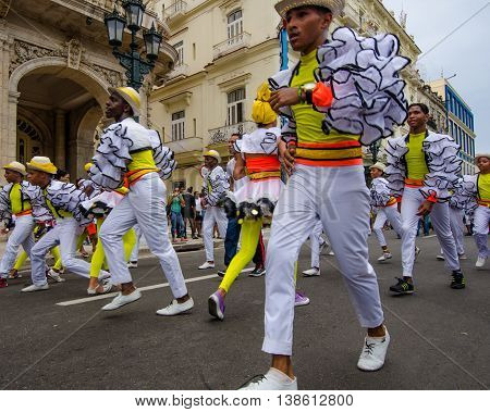 HAVANA - CUBA JUNE 9, 2016: Men in colorful costumes celebrate Havana Day marching and dancing a parade along Paseo de Marti in the historic La Habana Vieja neighborhood.