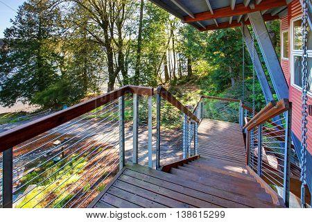 Covered Walkway Of Amazing Lake House With Greenery.