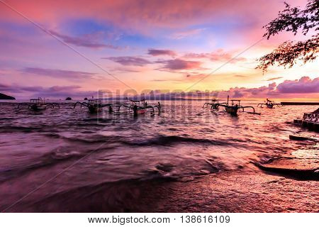 Pink sunset over fishing boats in Bali