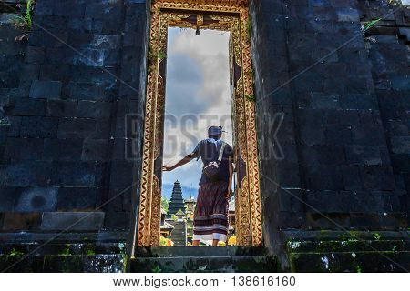 A Balinese man gazes through a doorway to a hindu temple