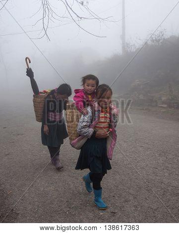 HA GIANG, VIETNAM, February 14, 2016 Hmong ethnic group of children, highland Ha Giang, Vietnam. Walking in the fog, winter