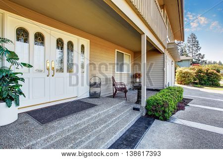 Spacious Entrance Porch With White Double Front Doors Of Luxury Home.