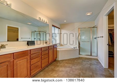 Nice Bathroom With Lots Of Space. Modern Brown Cabinets, Double Sink And Corner White Bath Tub