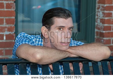 Middle age guy resting his chin on arms.