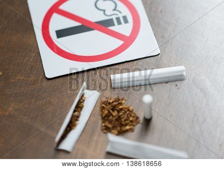 drug use, substance abuse, addiction and no smoking concept - close up of marijuana or handmade cigarette with prohibiting sign