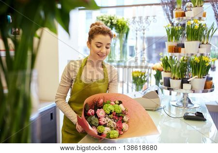 people, business, sale and floristry concept - happy smiling florist woman wrapping bunch into paper at flower shop