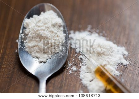 drug use, crime, addiction and substance abuse concept - close up of spoon and syringe with crack cocaine drug dose