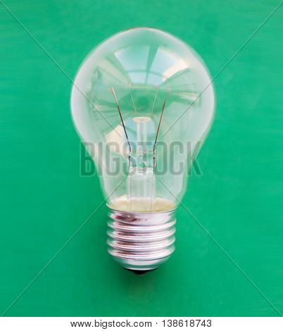 recycling, energy saving, electricity, environment and ecology concept - close up of lightbulb or incandescent lamp on green
