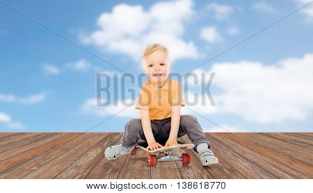 childhood, sport, leisure and people concept - happy little boy sitting on skateboard over blue sky and clouds background