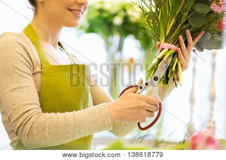 people, business, sale and floristry concept - close up of florist woman making bunch and cropping stems by scissors at flower shop