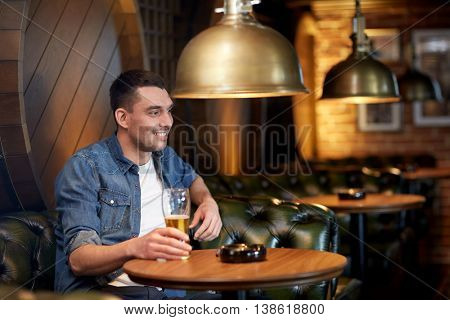 people, drinks, alcohol and leisure concept - happy young man drinking draft beer at bar or pub