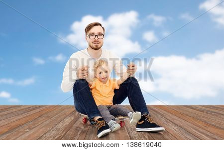 family, childhood, fatherhood, leisure and people concept - happy father and and little son on skateboard over blue sky and clouds background