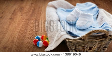 clothing, babyhood, motherhood and object concept - close up of white baby bootees with pile of clothes, towel and rattle for newborn boy in basket on wooden floor background