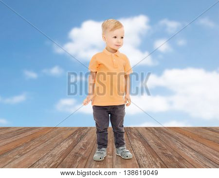 childhood, fashion and people concept - happy little boy in casual clothes over blue sky and clouds background