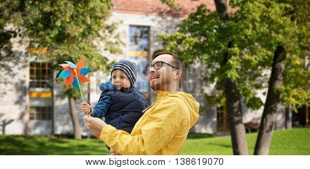 family, childhood, fatherhood, leisure and people concept - happy father and little son with pinwheel toy outdoors over summer city yard background