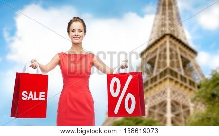 sale, discount, tourism and holidays concept - smiling young woman in red dress with shopping bags with percent sign over paris eiffel tower background