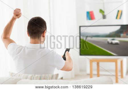 leisure, technology, motorsports, sport and people concept - man with remote control watching car racing on tv at home