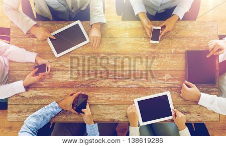 business, people, technology and team work concept - close up of creative team with smartphones and tablet pc computers sitting at table in office