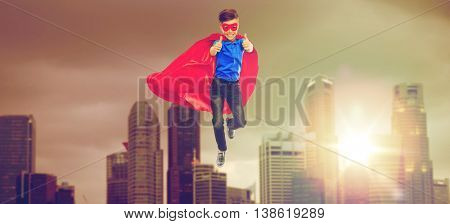 happiness, freedom, childhood, movement and people concept - boy in red superhero cape and mask flying in air and showing thumbs up over singapore city skyscrapers background