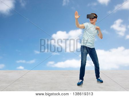 3d technology, virtual reality, entertainment, cyberspace and people concept - young man with virtual reality headset or 3d glasses playing game and fighting over blue sky and clouds background