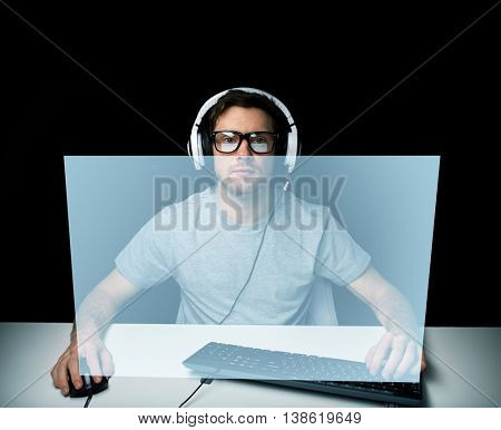 technology, gaming, let's play and people concept - young man or hacker in headset and eyeglasses with pc computer playing game and streaming playthrough or walkthrough video with virtual screen