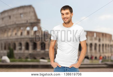 travel, tourism and people concept - handsome man in blank white t-shirt over coliseum background