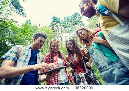 technology, travel, tourism, hike and people concept - group of smiling friends walking with backpacks and tablet pc computer looking for location in woods